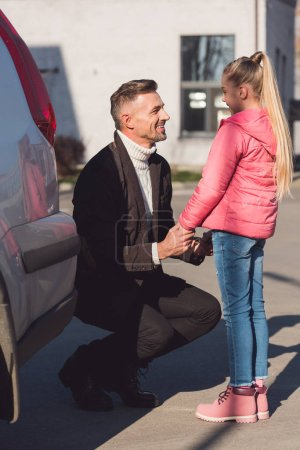 Father holding hands of daughter on street