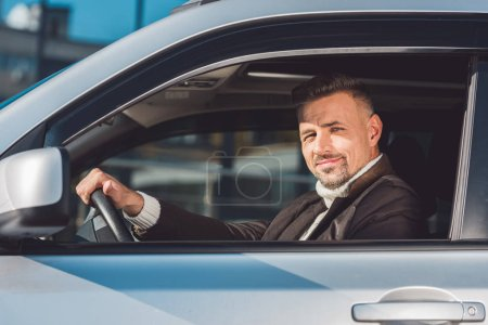 Photo for Handsome man holding steer and sitting in car - Royalty Free Image
