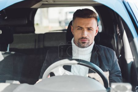 Handsome man in sweater and jacket sitting in car