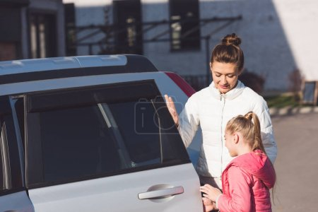 Mom opening car door and standing with daughter