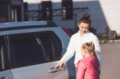 Mother opening car door and standing with daughter on street