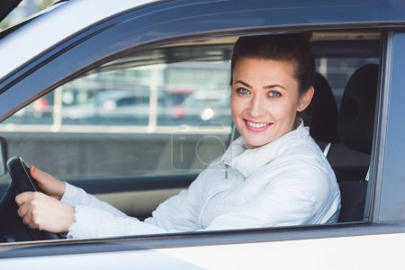 Beautiful woman sitting in car and holding steering wheel
