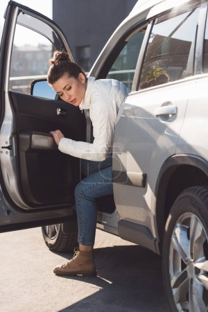 Woman in casual clothing getting out of car in daytime