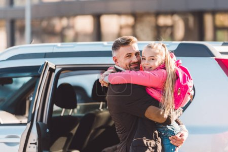 Father holding daughter and standing near car