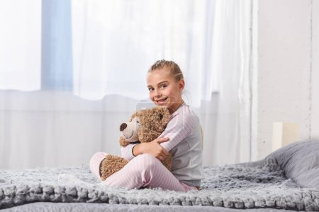 Cheerful kid holding teddy bear and sitting on bed
