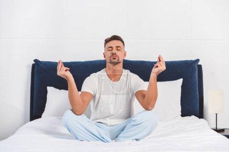 Photo pour Bel homme pratiquant l'yoga en pyjama - image libre de droit