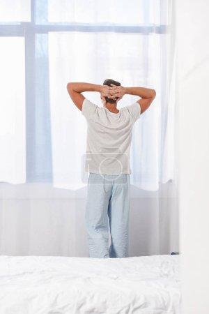 Photo pour Vue arrière de l'homme debout dans les vêtements de nuit dans la chambre - image libre de droit