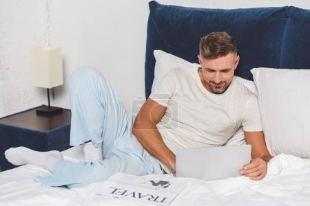 Handsome man using laptop and lying in bed