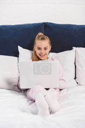 Cheerful preteen child using laptop in bedroom