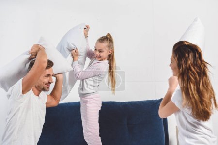 Cheerful parents having pillow fight with daughter in bedroom