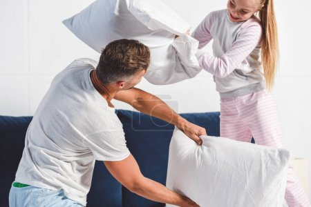 Photo for Dad and daughter having pillow fight at home - Royalty Free Image