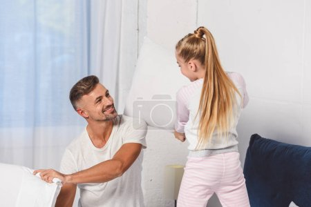 Father and daughter having pillow fight in bedroom