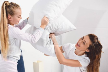Photo for Cheerful mother and daughter having pillow fight at home - Royalty Free Image
