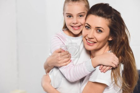 Mother and daughter hugging and smiling in bedroom