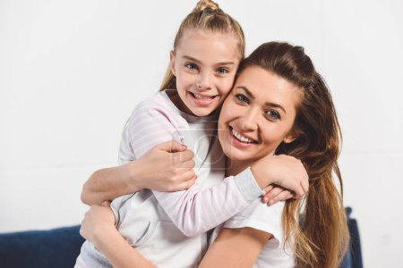 Photo for Mom and daughter embracing and smiling at home - Royalty Free Image