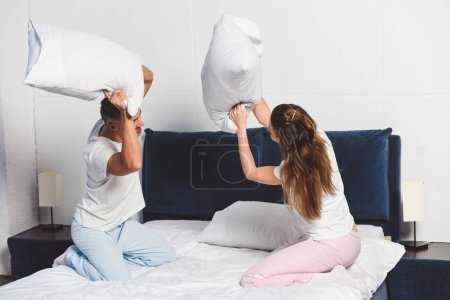 Cheerful couple having pillow fight in bedroom