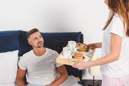Wife holding tray with breakfast and husband lying in bed