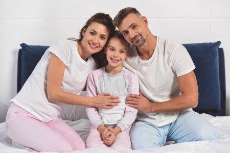 Foto de Familia sonriente en pijama sentado en la cama juntos - Imagen libre de derechos