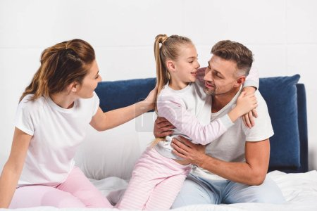 happy family in pajamas hugging in bed