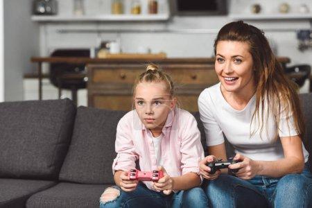 Photo pour Concentré de fille jeu vidéo avec mère souriante - image libre de droit