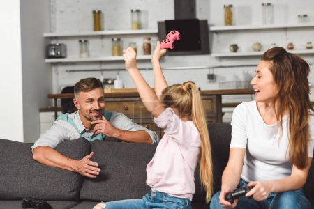 happy daughter rejoicing victory in video game while father sitting behind sofa