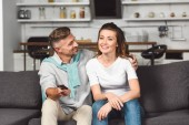husband and wife sitting on sofa and watching tv together while man looking at woman