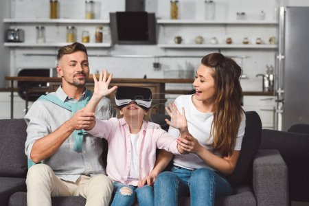 daughter sitting on sofa in virtual reality headset with parents