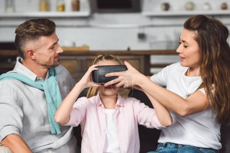 parents sitting on sofa and putting virtual reality headset on daughter head