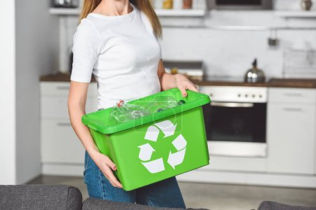 cropped view of woman holding green box with recycle sign and empty plastic bottles