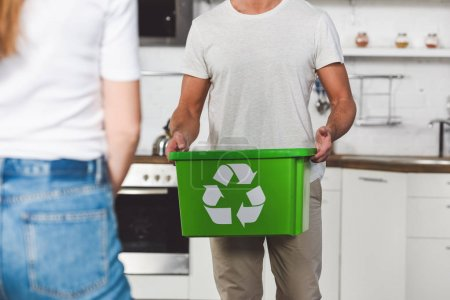 cropped with of man standing with green recycle box at kitchen