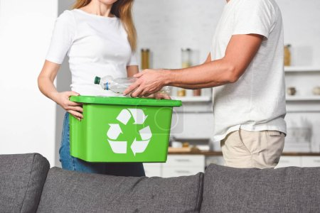 cropped view of adult couple putting empty plastic bottles in recycle green box