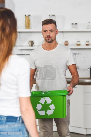 adult man holding green box with recycle sign and looking at woman