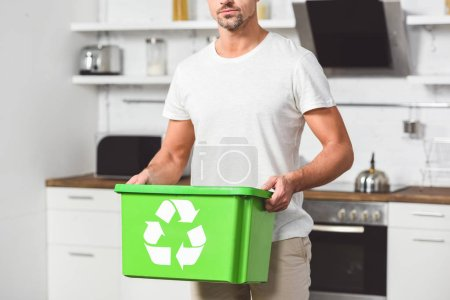 cropped view of man standing at kitchen with green recycle box