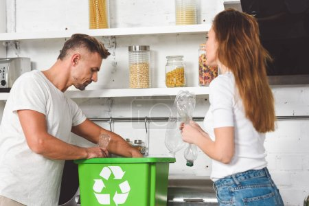 adult couple putting empty plastic bottles in green box with recycle sign