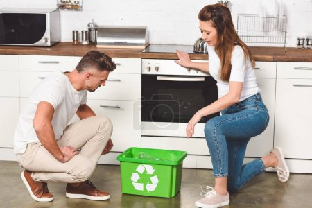 adult couple standing at kitchen with green recycle box on floor