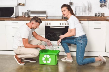 Adult couple putting empty plastic bottles in recycling green box at kitchen
