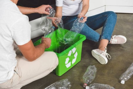 cropped view of couple sitting on floor and putting plastic bottles in green box at kitchen