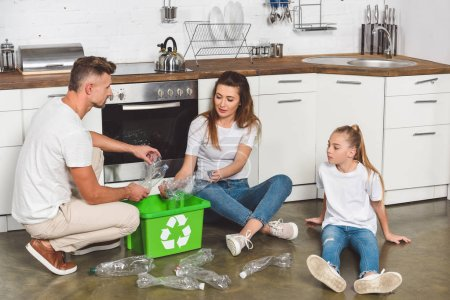 family sitting on floor at kitchen and putting empty plastic bottles in recycle box