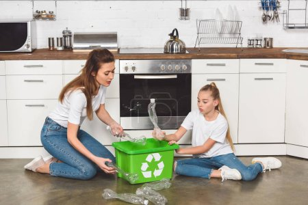 mother and daughter sitting on floor at kitchen and putting empty plastic bottles in box with recycle sign