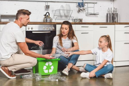 family sitting on floor at kitchen and putting empty plastic bottles in box with recycle sign