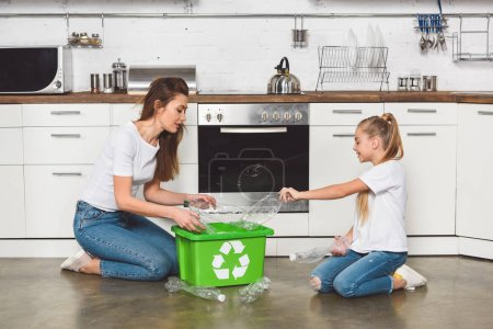 mother and daughter putting empty plastic bottles at green recycle box at kitchen