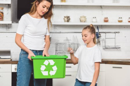 mother and daughter putting empty plastic bottles at green recycle box together