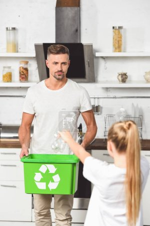 father holding green recycle box while daughter holding empty plastic bottles