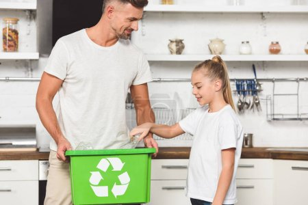 father and daughter putting empty plastic bottles at green recycle box together