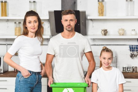 family standing at kitchen with green recycle box and looking at camera together