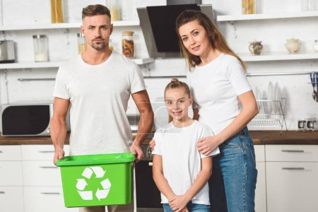 family standing at kitchen with green recycle box and looking at camera