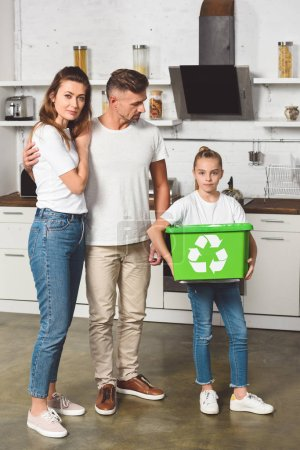 parents standing at kitchen while daughter holding green box with recycle sign