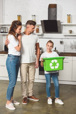 parents standing at kitchen while daughter holding green recycle box
