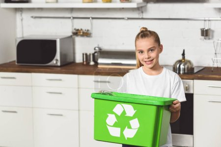 smiling child standing at kitchen with green recycle box