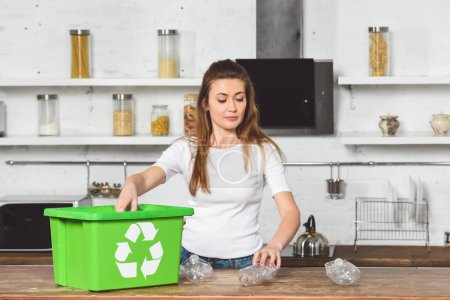 attractive woman putting plastic bottles in green recycle box at wooden table